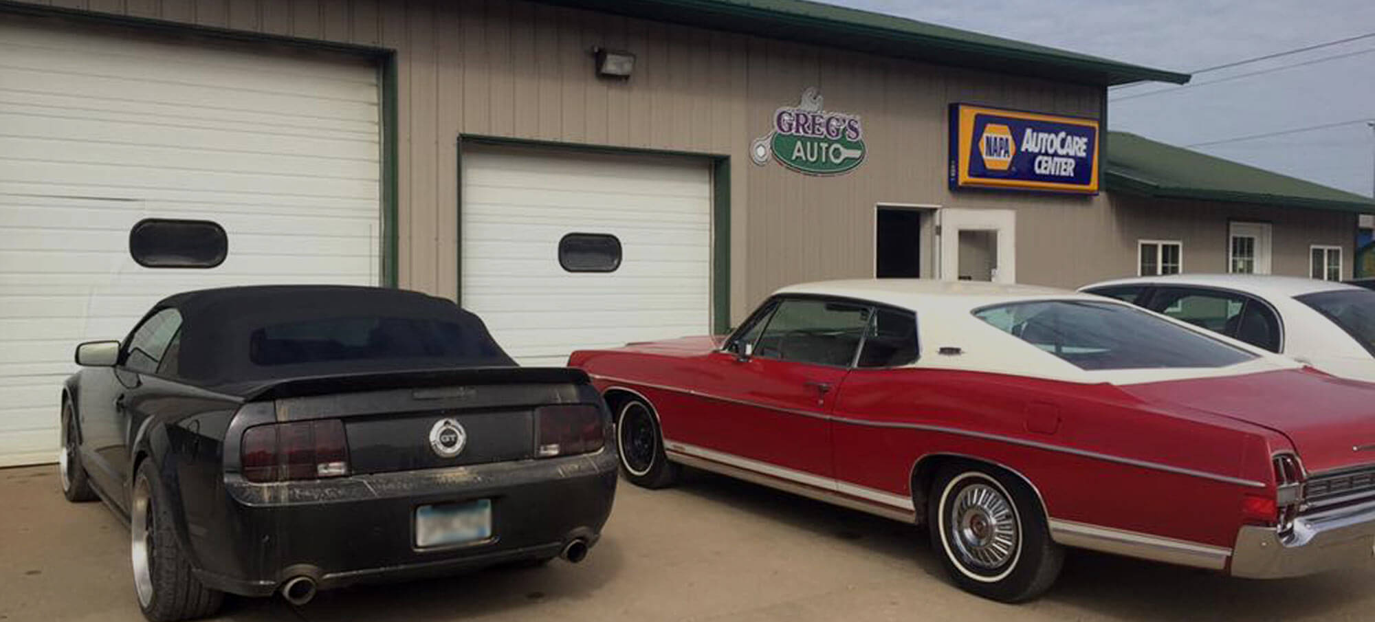 Exterior of Greg's Auto shop in Le Center with a mix of new, old, and classic cars parked in front of the auto bay doors